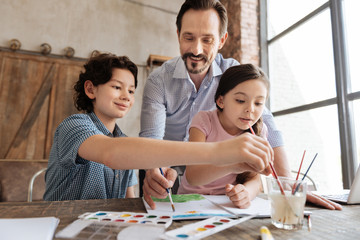 Pleasant family being immersed into painting process