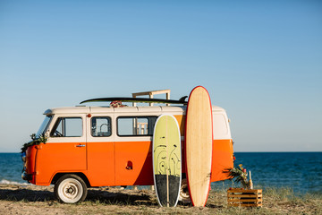 Printed roller blinds Vintage cars bus with a surfboard on the roof is a parked near the beach