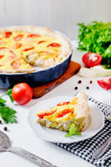 French open pie from short pastry, kish, tart with chicken, cherry tomatoes, greens and creamy cheese cress, filling, sauce and spices, pepper, lettuce and salt on white rustic background