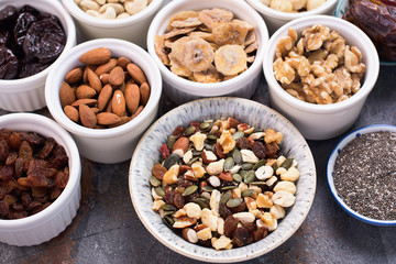 Ingredients for homemade paleo granola, different nuts and raisins, dates, seed on the grey stone background, top view