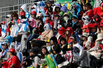 Spectators shield themselves from the sun during the Japanese F1 Grand Prix at the Suzuka circuit in Suzuka