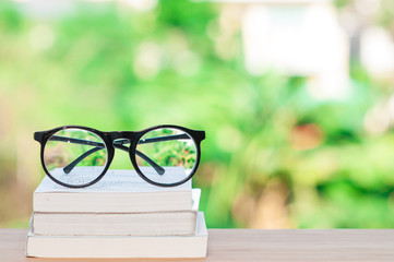Glasses and books on wooden table.