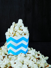Popcorn in a striped paper cup on a black background. Empty place for a text