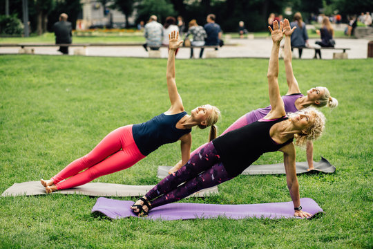 Diverse group of people outdoor in park on mats doing stretching exercises in a health and fitness concept. group of three blonde sporty women exercising outdoors