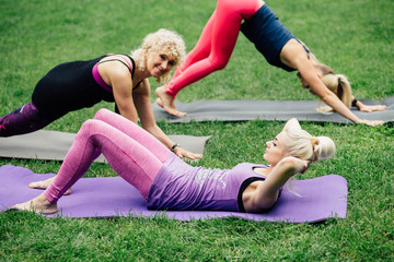 Diverse group of three female outdoor in park workout in a receding row on mats doing different exercises in a health and fitness concept. Group of three blonde sporty women exercising outdoors