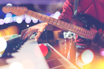 Guitar and piano keyboard detail.Live music and concert background.Guitarist on stage.Lifestyle of musicians and musical instrument.