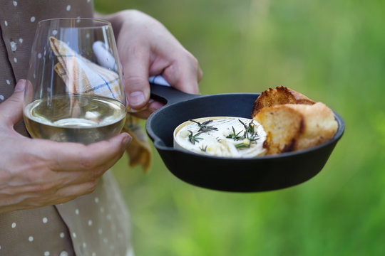 Baked camembert cheese  with garlic and rosemary in cast iron skillet