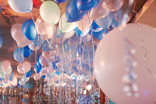 Festive decorated selling with blue tone helium balloons, birthday party