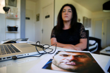"""Beatrice Huret, author of the book """"Calais mon Amour"""", poses with a photo of her Iranian lover Mokhtar at her home in Wierre-Effroy"""