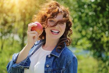 jolie femme rousse souriante mangeant une pomme dans la nature