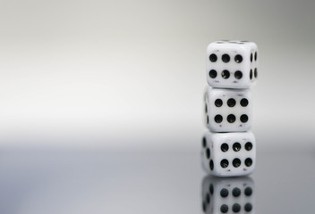Macro of three dice stack with six points and reflection
