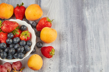 Strawberries, blueberries, apricot t on a wooden board