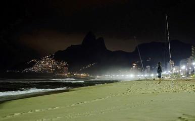 Men fish at night on Ipanema Beach in Rio de Janeiro