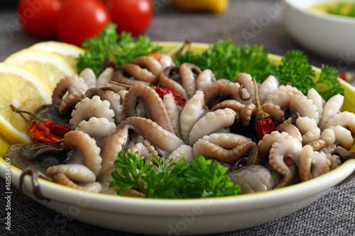 polpo o moscardini pesce crudo in piatto di ceramica sfondo tavolo ...