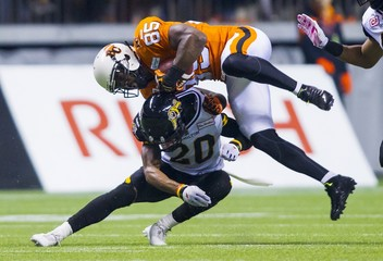 B.C Lions' Gore is up ended by Hamilton Tiger-Cats' Davis during their CFL football game in Vancouver