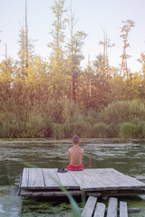 boy on the pier looking at the water. boy sitting on a wooden pier. view from the back. on the river calm and silence. on sunset