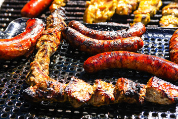 Close up of a BBQ grill with Bratwurst, chicken and seafood