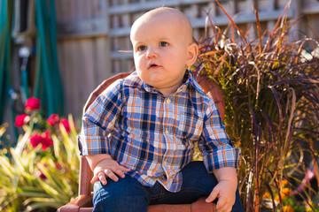 Baby Boy in Plaid Shirt Sitting in Backyard Garden