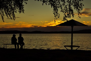 Two peopple are sitting on a bench on the beach and watching the sunset in summer