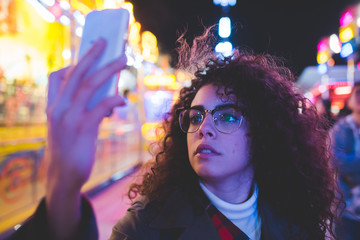 Portrait young woman mixed race taking selfie smart phone hand hold outdoor night life - social network,vanity, sharing concept