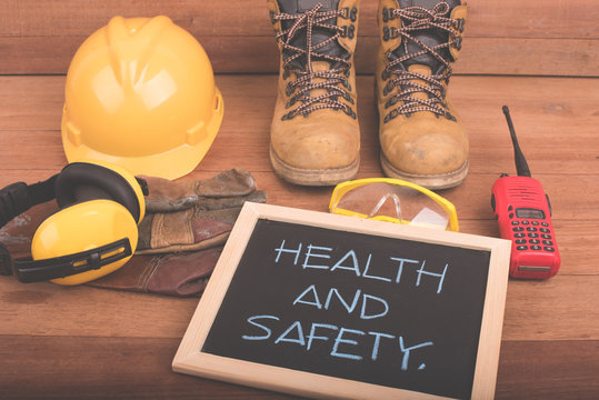 Standard construction safety equipment on wood background with health and safety text on blackboard.