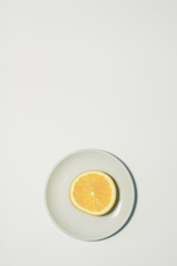 Minimal orange slice background. Fruit on white plate. Vertical design for a leaflet, banner, cover or flyer