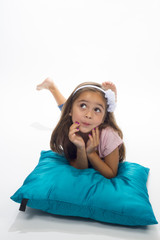 girl in studio lying on blue pillow posing to camera