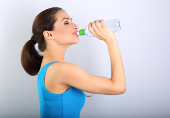 Beautiful happy sporty slim woman holding and drinking water from the bottle on blue background. Closeup portrait