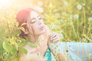 girl with fashionable makeup and beads in green leaves