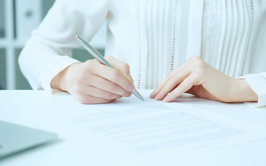 Businesswoman hands sign contract on desk. Female entrepreneur puts signature on official agreement. Profitable deal concept. Business partner accepts conditions. Shallow focus on signature.