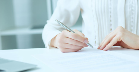 Businesswoman hands sign contract on desk. Female entrepreneur puts signature on official agreement. Profitable deal concept. Shallow focus on signature.