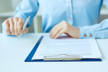 Hands of business woman signing the contract document with pen on desk. selective focus image on sign a contract.