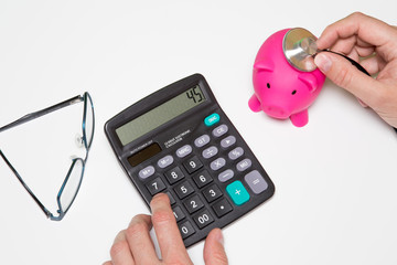 Money, home, finance and relationships concept - Doctor holding out your piggy bank wanting payment Savings Pay Bill,Stethoscope financial checkup or saving for medical insurance costs with calculator