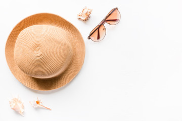 Sunglasses, summer straw hat beach and seashells on a white background with place for text