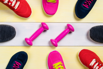 Scattered sports shoes on a multi-colored floor, in the middle lies a set of sports dumbbells