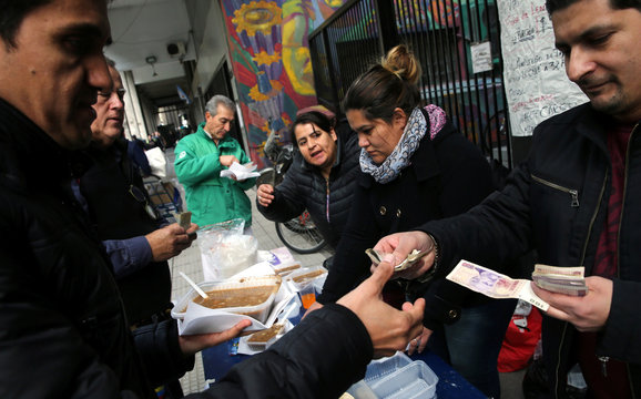 Workers who were fired from the Labor Ministry sell lentil soup outside the Ministry building in Buenos Aires