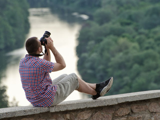 Man takes pictures from a hill in the background of forest and river