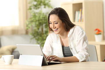 Woman writing in a tablet pc at home