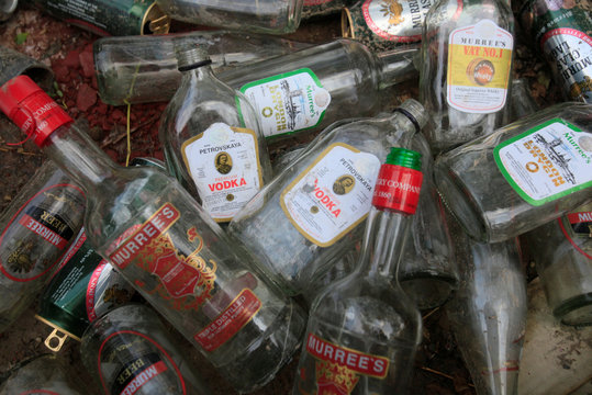 Used bottles of liquor and beer cans made by local brand Murree Brewery are seen at a garbage dump along a street in Lahore,