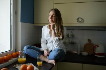 Serene morning woman in the kitchen, orange juice, oranges