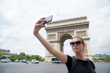 young woman making selfie in front of Triumphal arch