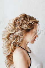 Beautiful woman with dyed hair with Evening hairstyle Greek braid