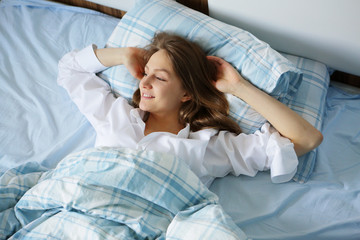 Smiling young woman in white shirt, lying in bed, good morning