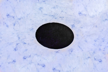 Blue background of marble and black oval in the middle for text