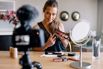 Young female vlogger recording a make-up broadcast for her vlog.