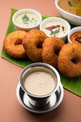 Frothy South Indian coffee or tea served in traditional steel glass - having south indian food vada sambar and chutney in the background, selective focus