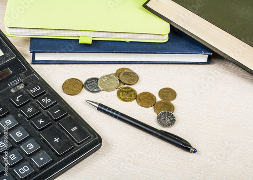 home savings budget concept notepad pen calculator and coins on