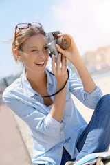 Cheerful girl taking pictures of the beach, tourist area