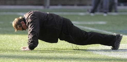 Edmonton Eskimos' head coach Chris Jones does pushups during practice ahead of the CFL 103rd Grey Cup championship football game in Winnipeg