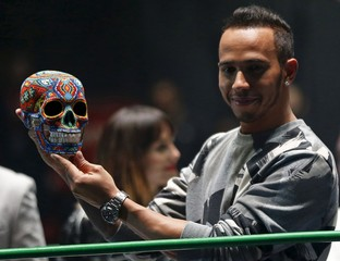 Mercedes Formula One driver Lewis Hamilton of Britain holds up at a traditional Day of the Dead Mexican skull at the Coliseo Arena during a promotional event in Mexico City